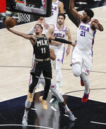 Atlanta Hawks guard Trae Young (11) draws a foul from Philadelphia 76ers center Joel Embiid (21) in the final minute of Game 4 of a second-round NBA basketball playoff series on Monday, June 14, 2021, in Atlanta. (Curtis Compton/Atlanta Journal-Constitution via AP)