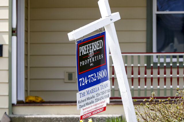 FILE This April 16, 2020 photo shows a real estate company sign marking a home for sale in Harmony, Pa. U.S. homeowners are seizing on historically low mortgage rates to refinance their mortgages. Refinancing is outpacing home purchase loans as job losses and economic uncertainty put off would-be buyers.   (AP Photo/Keith Srakocic)