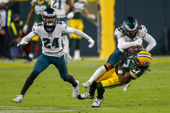 Green Bay Packers' Davante Adams catches a pass with Philadelphia Eagles' Avonte Maddox and Darius Slay (24) defending during the second half of an NFL football game Sunday, Dec. 6, 2020, in Green Bay, Wis. (AP Photo/Matt Ludtke)