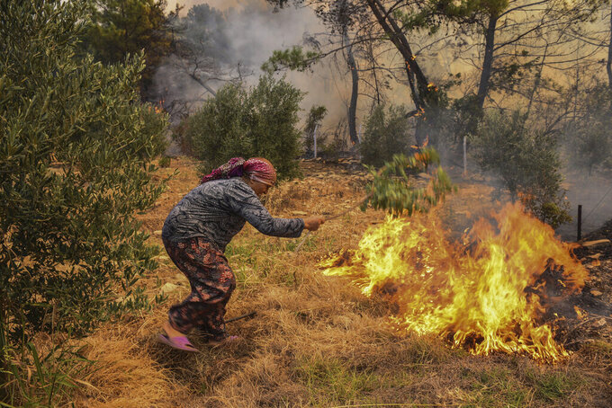 A woman tries to stop an advancing wildfire in Kacarlar village near the Mediterranean coastal town of Manavgat, Antalya, Turkey, Saturday, July 31, 2021. The death toll from wildfires raging in Turkey's Mediterranean towns rose to six Saturday after two forest workers were killed, the country's health minister said. Fires across Turkey since Wednesday burned down forests, encroaching on villages and tourist destinations and forcing people to evacuate. (AP Photo)