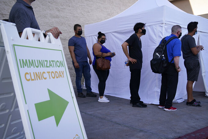 FILE- In this Wednesday, July 7, 2021, file photo, people wait in line for COVID-19 vaccinations at an event at La Bonita market, a Hispanic grocery store, in Las Vegas. The U.S. surgeon general said Sunday, July 18 that he's concerned about what lies ahead with cases of COVID-19 increasing in every state, millions still unvaccinated and a highly contagious virus variant spreading rapidly.. (AP Photo/John Locher, File)
