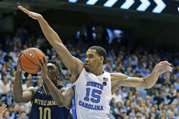 FILE - In this Jan. 15, 2019, file photo, North Carolina's Garrison Brooks (15)  defends against Notre Dame's TJ Gibbs (10) during the second half of an NCAA college basketball game, in Chapel Hill, N.C. Brooks returns after providing reliable defense and rebounding in the paint for the Tar Heels. (AP Photo/Gerry Broome, File)