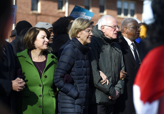 Democratic presidential rivals Amy Klobuchar, Elizabeth Warren and Bernie Sanders link arms during a Martin Luther King Jr. Day march on Monday, Jan. 20, 2020, in Columbia, S.C. (AP Photo/Meg Kinnard)