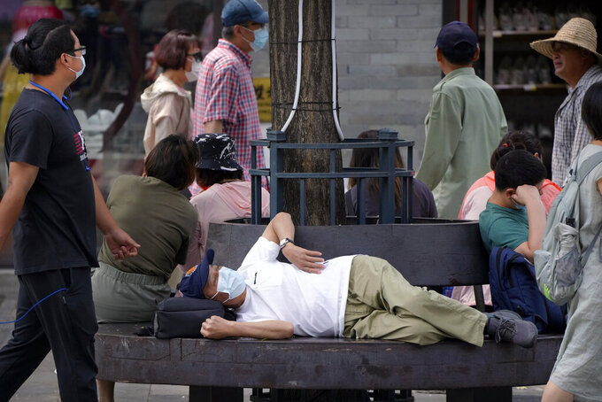 A man wearing a face mask to protect against COVID-19 rests on a bench at a tourist shopping street in Beijing, Tuesday, Aug. 3, 2021. Chinese authorities announced Tuesday mass coronavirus testing in Wuhan as an unusually wide series of COVID-19 outbreaks reached the city where the disease was first detected in late 2019. The current outbreaks, while still in the hundreds of cases in total, have spread much more widely than previous ones, reaching multiple provinces and cities including the capital, Beijing. (AP Photo/Mark Schiefelbein)