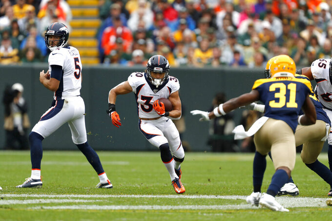 Denver Broncos running back Phillip Lindsay, center, runs between quarterback Joe Flacco (5) and Green Bay Packers strong safety Adrian Amos (31) during the first half of an NFL football game Sunday, Sept. 22, 2019, in Green Bay, Wis. (AP Photo/Matt Ludtke)