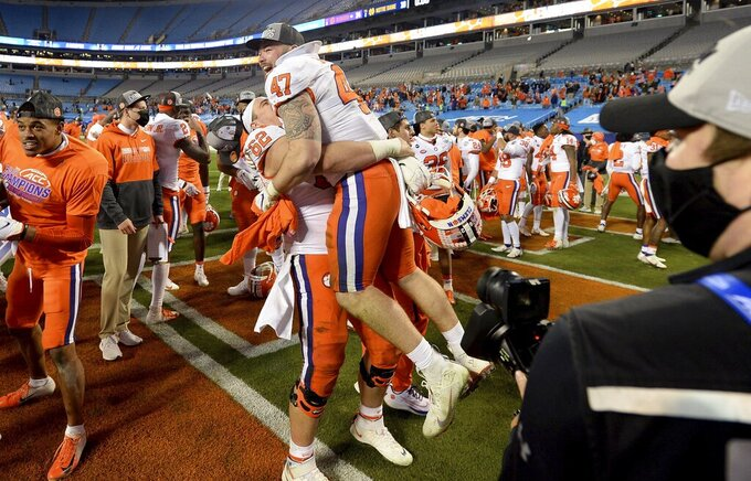 Clemson lineman Cade Stewart, center, lifts linebacker James Skalski following the team's victory in the Atlantic Coast Conference championship NCAA college football game against Notre Dame, Saturday, Dec. 19, 2020, in Charlotte, N.C. (Jeff Siner/The News & Observer via AP)