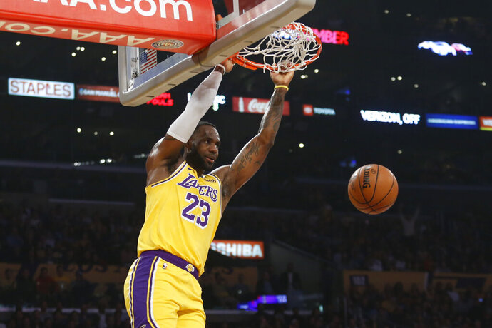 Los Angeles Lakers' LeBron James dunks during the first half of the team's NBA basketball game against the Oklahoma City Thunder on Tuesday, Nov. 19, 2019, in Los Angeles. (AP Photo/Ringo H.W. Chiu)