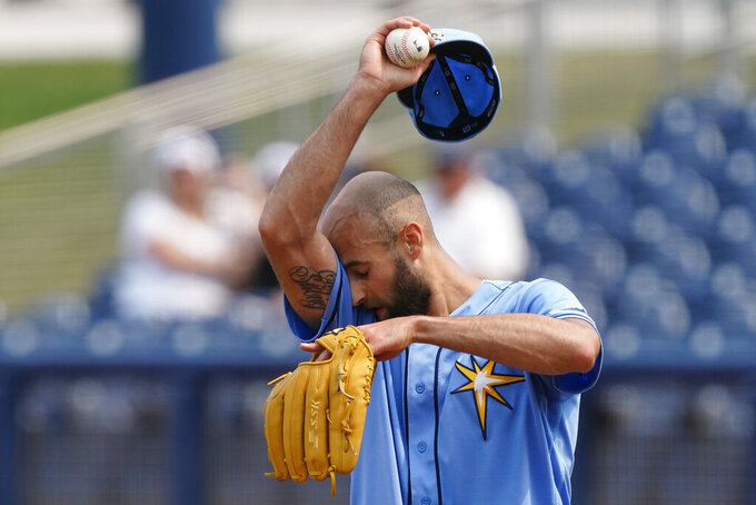 Tampa Bay Rays relief pitcher Nick Anderson wipes his face as he works in the sixth inning of a spring training baseball game against the Minnesota Twins on Wednesday, March 24, 2021, in Port Charlotte, Fla. (AP Photo/John Bazemore)