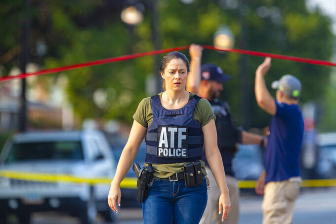 ATF agents work the scene of a shooting on South Ashland Avenue near West 118th Street next to Interstate 57, July 7, 2021.  Police say three undercover law enforcement officers were shot and wounded while driving onto an expressway on Chicago's South Side.  (Vashon Jordan Jr./Chicago Tribune via AP)