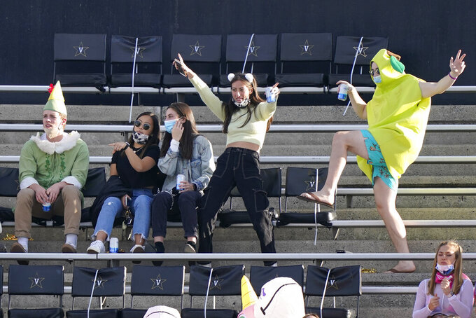 Vanderbilt students wear Halloween costumes and watch from seats assigned for social distancing as they watch Vanderbilt play Mississippi in the first half of an NCAA college football game Saturday, Oct. 31, 2020, in Nashville, Tenn. (AP Photo/Mark Humphrey)