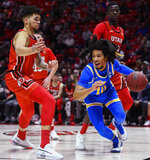 UCLA guard Tyger Campbell drives between Utah forward Timmy Allen, left, and center Lahat Thioune, right rear, during the first half of an NCAA college basketball game Thursday, Feb. 20, 2020, in Salt Lake City. (AP Photo/Alex Goodlett)