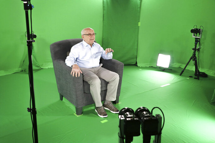 This August 2018 photo shows Holocaust survivor Max Glauben sitting in an interactive green screen room while filming a piece for the Dallas Holocaust Museum in Dallas. Glauben will be the latest to have his story recorded in such a way that generations to come will be able to ask his image questions. Glauben, who turns 91 on Monday, had lost his mother, father and brother at the hands of the Nazis when U.S. troops rescued him while he was on a death march. (McGuire Boles/Dallas Holocaust Museum via AP)