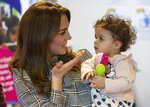 Britain's Kate, Duchess of Cambridge, talks with 18-month-old Sorayah Ahmad during a visit to a Khidmat Centre in Bradford, England, Wednesday, Jan. 15, 2020. (Charlotte Graham/Pool Photo via AP)