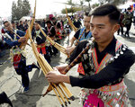 David Vue, right, and others perform with the qeej, a traditional bamboo flute, during the parade kicking off the first day of the Hmong New Year celebration at the Fresno Fairgrounds, Thursday Dec. 26, 2019.  (John Walker/The Fresno Bee via AP)