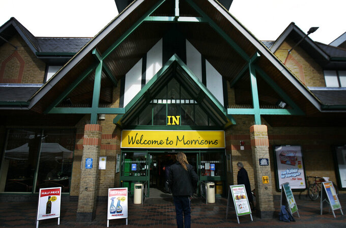 FILE - In this Thursday March 12, 2009 file photo, people enter a Morrisons supermarket in west London. Shares in British supermarket chain Morrisons have spiked higher after New York-based private equity firm Clayton, Dubilier & Rice trumped a previous offer for the company with a 7 billion-pound ($9.5 billion) bid, it was announced Friday, Aug. 20, 2021. Morrisons' board has accepted the offer and said shareholders should vote in favor of the takeover at a meeting due in early October. (AP Photo/Lefteris Pitarakis, file)