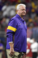 LSU Offensive Coordinator Steve Ensminger watches teams warm up before the first half of the Peach Bowl NCAA semifinal college football playoff game between LSU and Oklahoma, Saturday, Dec. 28, 2019, in Atlanta. Ensminger's daughter-in-law, Carley McCord, died in a plane crash Saturday in Louisiana on the way to the game. (AP Photo/Danny Karnik)