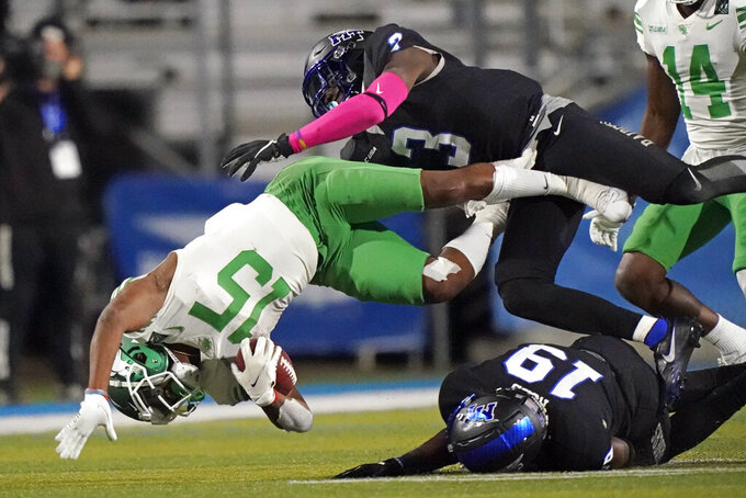 North Texas running back Tre Siggers (15) is brought down by Middle Tennessee defenders Gregory Grate Jr. (3) and Teldrick Ross (19) in the second half of an NCAA college football game Saturday, Oct. 17, 2020, in Murfreesboro, Tenn. (AP Photo/Mark Humphrey)