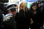"FILE - In this file photo dated Monday, Dec. 23, 2019, Love Island TV presenter Caroline Flack, centre, is escorted by police as she arrives at court in London, after being charged with assault of former professional tennis player and model Burton. The host of controversial reality TV show ""Love Island,"" has died aged 40, according to a statement from her family Saturday Feb. 15, 2020. (AP Photo/Petros Karadjias, FILE)"