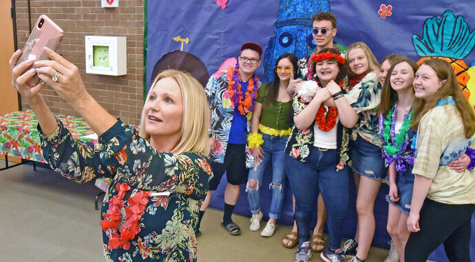 This photo taken May 8, 2019, shows North Dakota first lady Kathryn Burgum, left, taking a group selfie with students at Century High School before classes on during the launch of CHS Corner, a one-stop, user-friendly website created by Rachel Roehrich that connects students with mental health and addiction resources. The students, from left, are Brock Voegele, Kaitlyn, Justice Coleman, Roehrich, Oriana Richter, Emily Kuntz, Brooklyn Richter and Irie Thompson.  (Tom Stromme/The Bismarck Tribune via AP)