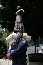 A police officer stands guard near a statue of independence heroine Leona Vicaria on Paseo de la Reforma in Mexico City, Sunday, September 13, 2020. Mexico will celebrate its day of Independence from Spain on September 16. (AP Photo/Marco Ugarte)