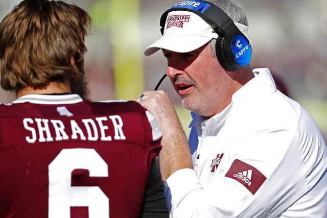 Mississippi State head coach Joe Moorhead, right, confers with quarterback Garrett Shrader (6) during the second half of an NCAA college football game against Alabama in Starkville, Miss., Saturday, Nov. 16, 2019. Alabama won 38-7. (AP Photo/Rogelio V. Solis)