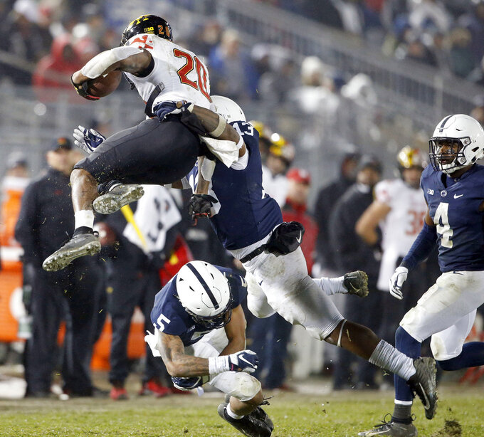 Penn State's Ellis Brooks (13) and Tariq Castro-Fields (5) bring down Maryland's Javon Leake (20) during the second half of an NCAA college football game in State College, Pa., Saturday, Nov. 24, 2018. Penn State won 38-3. (AP Photo/Chris Knight)