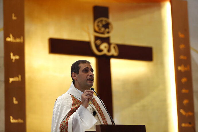 Lebanese priest Marwan Mouawad, speaks during Sunday Mass at Saint Maron-Baouchrieh Church that was damaged by last Tuesday's explosion that hit the Beirut seaport, in Baouchrieh neighborhood in Beirut, Lebanon, Sunday, Aug. 9, 2020. In interviews with The Associated Press, Father Rabih Thoumy and church priest Father Marwan Mouawad recount the horror of the moment the blast rocked the church. Thoumy says: