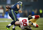 File-This Jan. 19, 2014, file photo shows San Francisco 49ers outside linebacker Aldon Smith (99) knocking the ball loose from Seattle Seahawks quarterback Russell Wilson (3) for a fumble recovered by the 49ers in the first quarter during the NFL football NFC Championship game in Seattle. As part of its celebration of its 100th season, the NFL is designating a Game of the Week, each chosen to highlight a classic matchup. For this week, it's the 49ers-Seahawks game. To mark each Game of the Week, the AP will be reprinting its story of a classic matchup in the rivalry. This week it's the Seattle Seahawks' 23-17 win over the San Francisco 49ers in the NFC championship game on Jan. 19, 2014.  (Paul Kitagaki Jr./The Sacramento Bee via AP, File)/The Sacramento Bee via AP)
