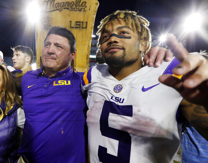 FILE - In this Oct. 21, 2017, file photo, LSU head coach Ed Orgeron, left, celebrates with running back Derrius Guice (5) following a win over Mississippi in an NCAA college football game in Oxford, Miss. A 74-year-old woman told state lawmakers she spoke directly to Orgeron about sexual harassment she endured in 2017 from one of his star players. But the woman, a grandmother, said Orgeron did nothing to reprimand then-LSU running back Guice when the player allegedly harassed her while she working at her Superdome security job in 2017. (AP Photo/Rogelio V. Solis, File)
