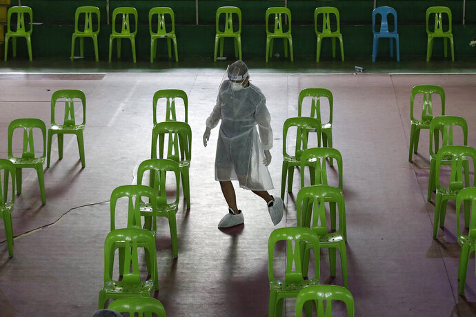 A health worker wearing a protective suit checks chairs before they open a free COVID19 swab testing at a gymnasium in Navotas city, Philippines on Thursday, Aug. 6, 2020. The capital and outlying provinces returned to another lockdown after medical groups warned that the country was waging a losing battle against the coronavirus amid an alarming surge in infections. (AP Photo/Aaron Favila)