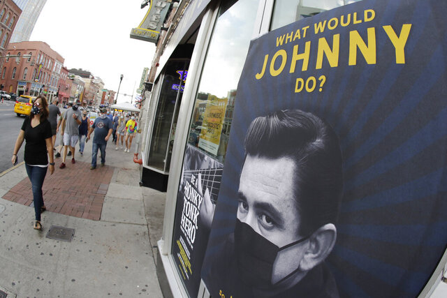 A poster showing country music legend Johnny Cash wearing a mask is attached to a storefront Wednesday, Aug. 5, 2020, in Nashville, Tenn. The wearing of face coverings is required in most public indoor and outdoor situations in Nashville due to an increase of COVID-19 cases. (AP Photo/Mark Humphrey)