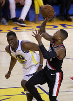 Portland Trail Blazers guard Damian Lillard, right, shoots against Golden State Warriors center Kevon Looney during the first half of Game 1 of the NBA basketball playoffs Western Conference finals in Oakland, Calif., Tuesday, May 14, 2019. (AP Photo/Jeff Chiu)