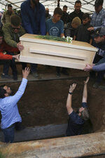 The coffin that contains the remains of 12-year-old Howard Jacob Miller Jr. is lowered into a grave at the cemetery in Colonia Le Baron, Mexico, Friday, Nov. 8, 2019, during a burial service for Rhonita Miller and four of her young children, who were murdered by drug cartel gunmen. The bodies of Miller and four of her children were taken in a convoy of pickup trucks and SUVS, on the same dirt-and-rock mountainous road where they were killed Monday, for burial in the community of Colonia Le Baron in Chihuahua state. (AP Photo/Marco Ugarte)