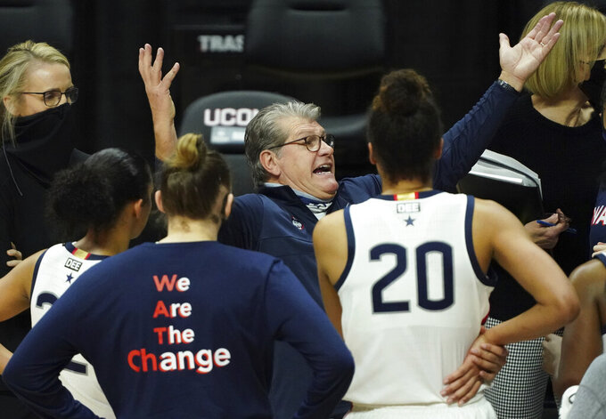 Connecticut head coach Geno Auriemma, center, talks to his team during a break in the second half against the Marquette during an NCAA college basketball game Monday, March 1, 2021, in Storrs, Conn. (David Butler II/Pool Photo via AP)