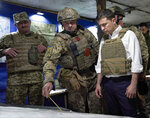 FILE - In this file photo taken on Oct. 14, 2019, Ukrainian President Volodymyr Zelenskiy, right, listens to a serviceman as he visits the war-hit Donetsk region, eastern Ukraine. Ukraine is at the center of a major geopolitical battle in the eastern part of the country with Moscow backed separatists. Facing that reality, Zelenskiy is reaching out to Russia directly in a bid to end the conflict before things get worse. (Ukrainian Presidential Press Office via AP, File)