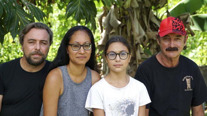 A group who have been stranded in Tahiti, pictured from left, Benjamin Baude, Kissy Ika Chavez Baude, Gaïa Baude Ika and Thierry Gourtay in Afareaitu on Moorea Island, Tahiti, Saturday, Sept. 19, 2020. A group of 25 residents from remote Easter Island has been stranded far from home for six months now. Many arrived in March planning to stay for just a few weeks. But they got stuck when the virus swept across the globe and their flights back home on LATAM airlines were canceled. LATAM says it doesn't know when it will restart the route.(Teraihau Rio via AP)