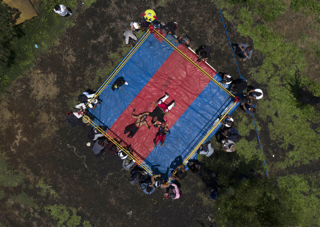 """Mexican Lucha Libre wrestlers perform an exhibition fight for the media, as they train for what will be live streaming events which they will charge for, at Xochimilco's famous floating gardens on the outskirts of Mexico City, Saturday, Aug. 22, 2020, amid the new coronavirus pandemic. Few of Mexico's cultural traditions have been hit as hard by the coronavirus pandemic as """"lucha libre"""" wrestling. (AP Photo/Fernando Llano)"""