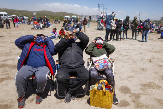 Viewers wear special glasses to watch a total solar eclipse in Piedra del Aguila, Argentina, Monday, Dec. 14, 2020. The total solar eclipse was visible from the northern Patagonia region of Argentina and from Araucania in Chile, and as a partial eclipse from the lower two-thirds of South America. (AP Photo/Natacha Pisarenko)