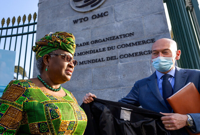 FILE - In this Monday, March 1, 2021 file photo, New Director-General of the World Trade Organisation Ngozi Okonjo-Iweala, left, walks at the entrance of the WTO, following a photo-op upon her arrival at the WTO headquarters to take office in Geneva, Switzerland. The World Trade Organization is raising its estimate for the rebound in global trade in goods but warning that the COVID-19 pandemic still poses the greatest threat to a recovery that is being hampered by lagging vaccinations, regional disparities and weakness in services. The organizations' WTO Director-General Ngozi Okonjo-Iweala called for a better access to vaccines for people in in poorer countries. (Fabrice Coffrini/Pool/Keystone via AP, FIle)