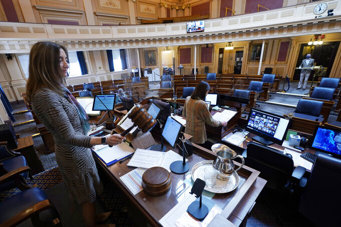 House speaker Del. Eileen Filler-Corn, D-Fairfax, gavels in the session to an empty Virginia House of Delegates chamber after a Zoom Legislative session at the Capitol in Richmond, Va., Wednesday, Feb. 10, 2021. (AP Photo/Steve Helber)