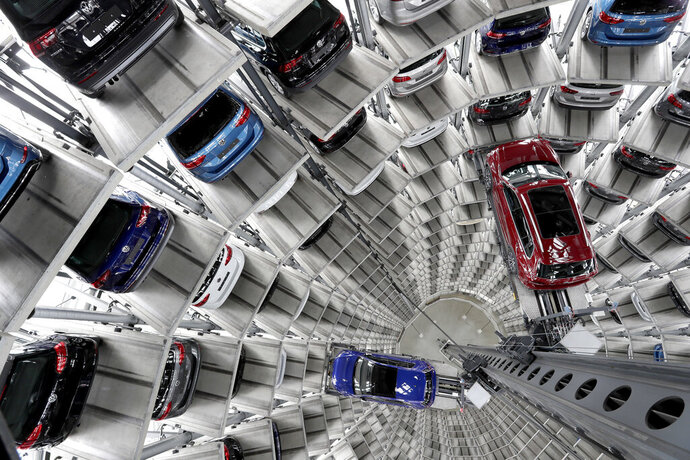 FILE - In this March 14, 2017 file photo Volkswagen cars are lifted inside a delivery tower of the company in Wolfsburg, Germany.  Volkswagen says its profits jumped 44% in the third quarter thanks to a more profitable mix of vehicles but warned that global markets are slowing more than expected and lowered its forecast for annual sales. (AP Photo/Michael Sohn, file)
