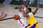 Los Angeles Lakers' Anthony Davis, right, drives into Toronto Raptors' Serge Ibaka (9) during the second half of an NBA basketball game Saturday, Aug. 1, 2020, in Lake Buena Vista, Fla. (AP Photo/Ashley Landis, Pool)