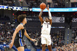 Connecticut's Christian Vital, right, shoots over Memphis' Lester Quinones during the second half of an NCAA college basketball game Sunday, Feb. 16, 2020, in Hartford, Conn. (AP Photo/Jessica Hill)