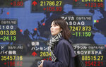 A woman walks by an electronic stock board of a securities firm in Tokyo, Monday, Nov. 19, 2018. Asian shares were mostly higher Monday after a buying spree on Wall Street kept up investor optimism into a new week, despite continuing worries about trade tensions. (AP Photo/Koji Sasahara)