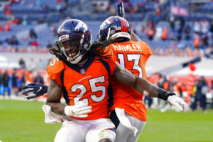 Denver Broncos running back Melvin Gordon (25) celebrates his rushing touchdown with teammate K.J. Hamler (13) during the second half of an NFL football game against the Miami Dolphins, Sunday, Nov. 22, 2020, in Denver. (AP Photo/David Zalubowski)