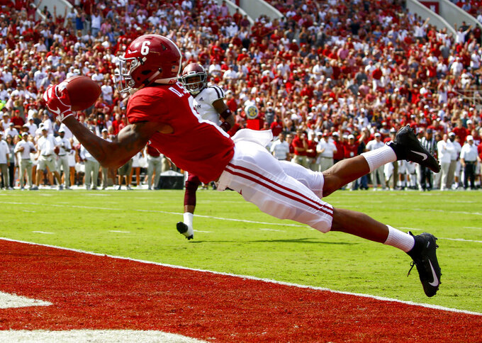 FILE - In this Sept. 22, 2018, file photo, Alabama wide receiver DeVonta Smith (6) catches a pass for a touchdown during the first half of an NCAA college football game against Texas A&M,  in Tuscaloosa, Ala. No. 1 Alabama has one of the SEC's most talented collection of receivers, and the Crimson Tide is spreading it around among Jerry Jeudy, Henry Ruggs III, DeVonta Smith and Jaylen Waddle. (AP Photo/Butch Dill, File)