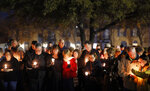 Church and community members gather outside West Freeway Church of Christ in White Settlement, Texas, for a candlelight vigil, Monday, Dec. 30, 2019. A gunman shot and killed two people before an armed security officer returned fire, killing him during their service on Sunday. (Tom Fox/The Dallas Morning News via AP)
