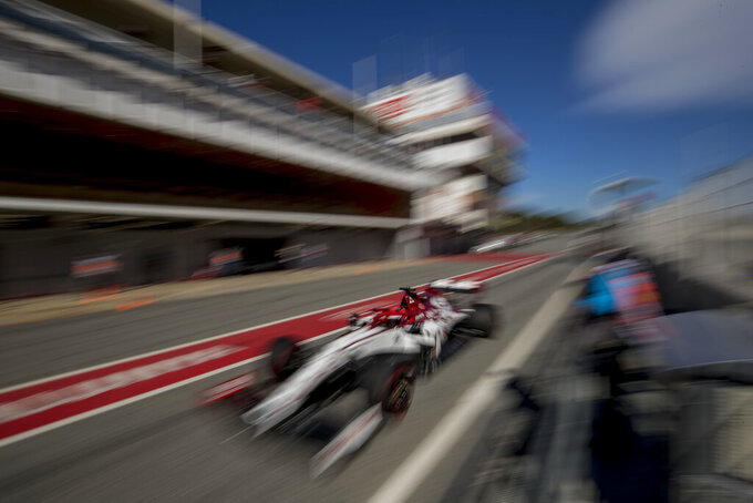 Test driver Robert Kubica drives the Alfa Romeo in the pit lane during the Formula One pre-season testing session at the Barcelona Catalunya racetrack in Montmelo, outside Barcelona, Spain, Wednesday, Feb. 26, 2020. (AP Photo/Joan Monfort)