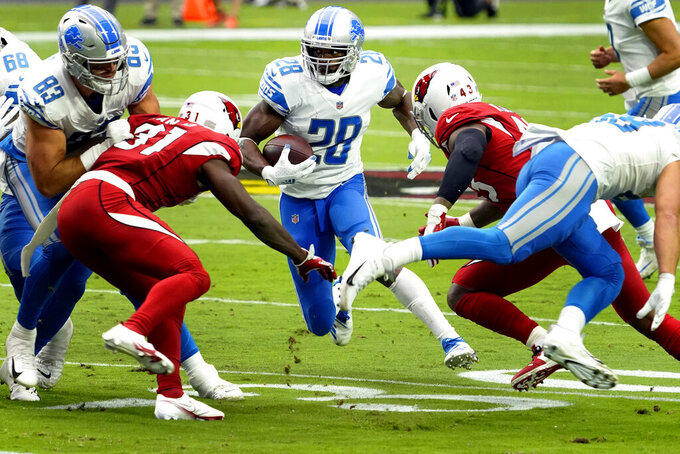 Detroit Lions running back Adrian Peterson (28) looks for an opening as Arizona Cardinals free safety Chris Banjo (31) defends during the first half of an NFL football game, Sunday, Sept. 27, 2020, in Glendale, Ariz. (AP Photo/Rick Scuteri)