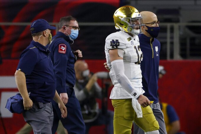 Notre Dame quarterback Ian Book is helped off the field by team medical personnel in the second half of the Rose Bowl NCAA college football game against Alabama in Arlington, Texas, Friday, Jan. 1, 2021. (AP Photo/Ron Jenkins)